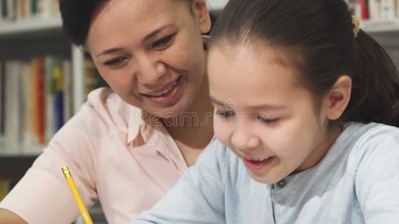 Feche acima de uma menina bonito que estuda com sua mãe imagens de stock royalty free