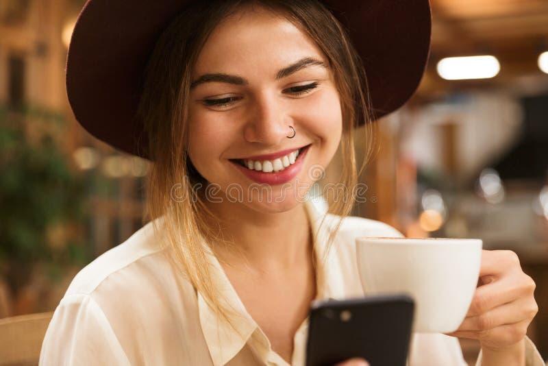 Feche acima de uma menina de sorriso no chapéu que senta-se na tabela do café dentro, guardando o copo do chá, usando o telefone  foto de stock