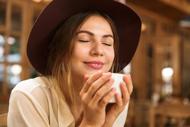 Feche acima de uma menina de sorriso no chapéu que senta-se na tabela do café dentro, guardando o copo do te fotografia de stock