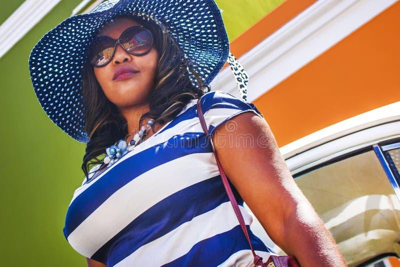 Feche acima de uma mulher africana bonita em um vestido listrado azul e branco na frente de um vintage Volkswagen Beetle e tradic foto de stock royalty free