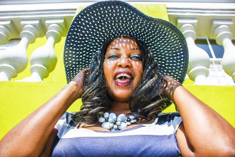 Feche acima de uma mulher africana bonita em um vestido listrado azul e branco que modela na frente de uma casa BO-Kaap tradicion fotografia de stock royalty free