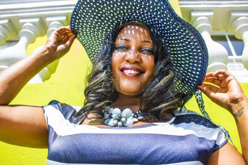 Feche acima de uma mulher africana bonita em um vestido listrado azul e branco que modela na frente de uma casa BO-Kaap tradicion foto de stock