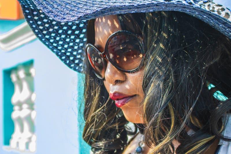 Feche acima de uma mulher africana bonita em um vestido listrado azul e branco que modela na frente das casas BO-Kaap tradicionai imagem de stock royalty free