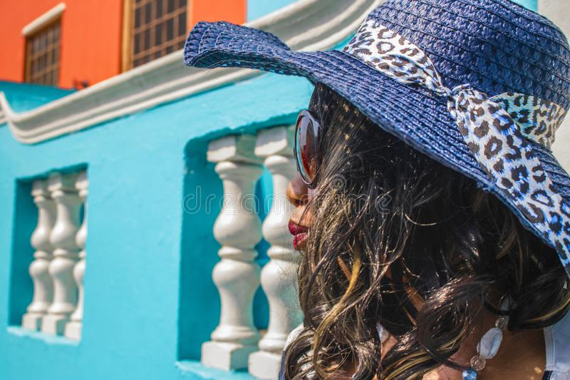Feche acima de uma mulher africana bonita em um vestido listrado azul e branco que modela na frente das casas BO-Kaap tradicionai imagens de stock royalty free