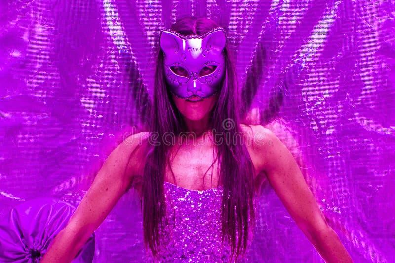 Feche acima de uma mulher bonita em uma máscara do gato em uma barraca de mylar sob a iluminação ultravioleta imagem de stock