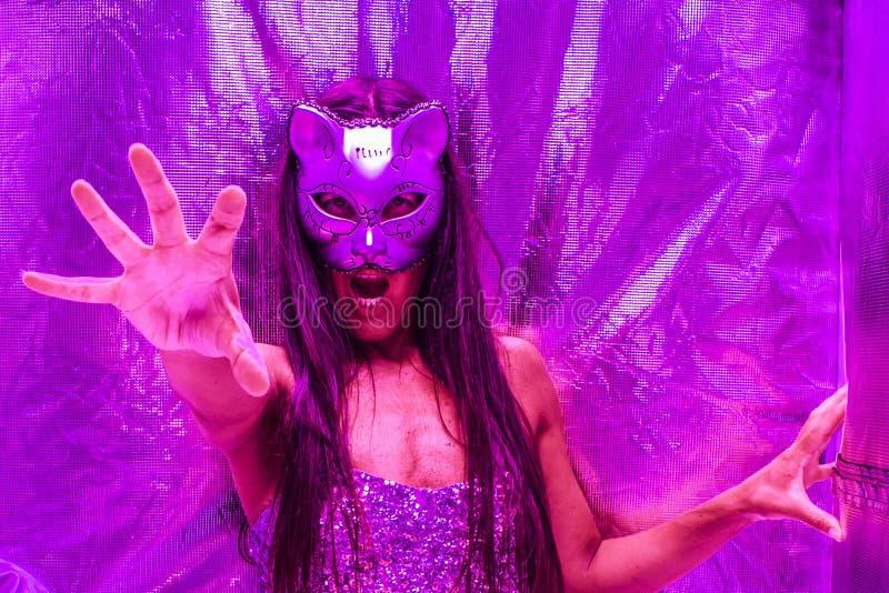 Feche acima de uma mulher bonita em uma máscara do gato em uma barraca de mylar sob a iluminação ultravioleta foto de stock royalty free