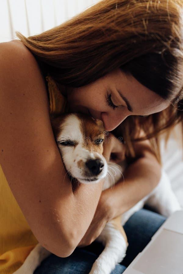 Feche acima de uma mulher bonita que beija seu cão Jack Russell Terrier no por do sol imagem de stock