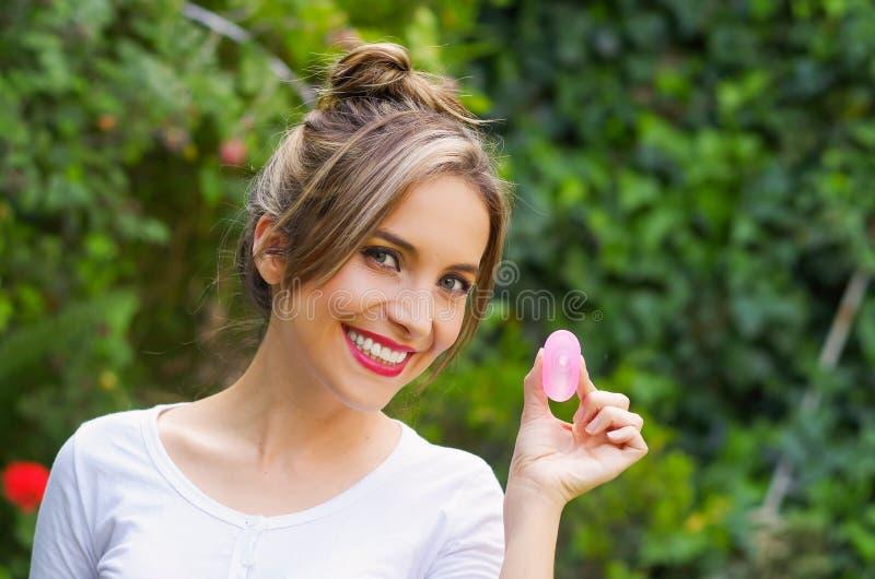 Feche acima de uma mulher bonita de sorriso dos jovens que guarda um copo menstrual em um conceito da ginecologia da mão, no borr fotografia de stock royalty free