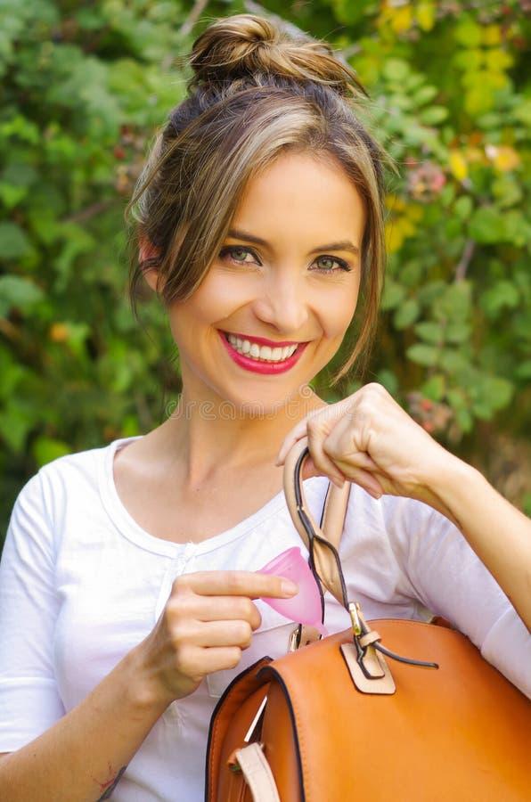 Feche acima de uma mulher bonita de sorriso dos jovens que mantém um copo menstrual dentro de uma bolsa Conceito da ginecologia,  fotografia de stock