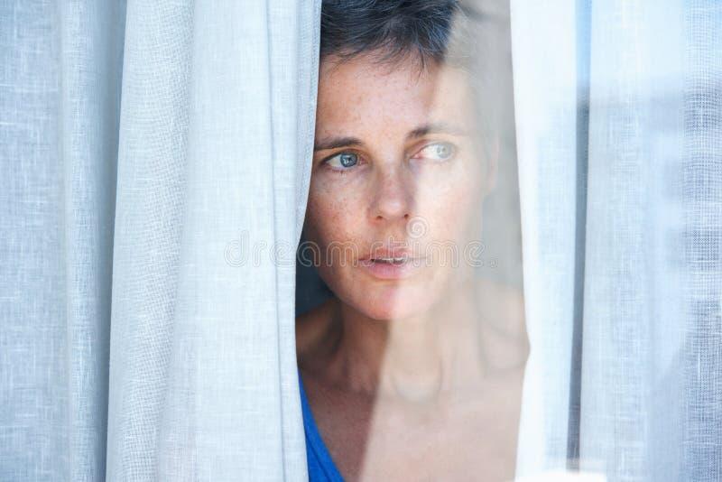 Feche acima de uma mulher mais idosa que olha cortinas de abertura e que olha através da janela foto de stock royalty free