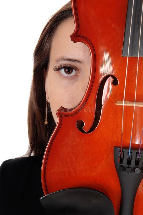 Feche acima de uma mulher que esconde atrás de um violino fotografia de stock