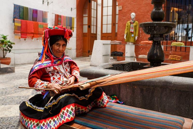 Feche acima de uma mulher tradicional que faz matérias têxteis peruanas para o sal imagens de stock
