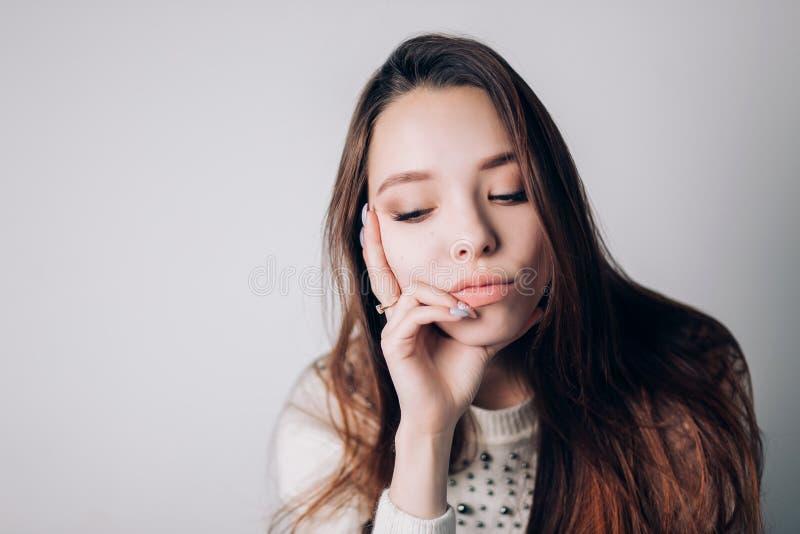 Feche acima de uma mulher triste e deprimida que olha ao lado A menina abaixou sua cabeça e pensamento sobre algo em um backgroun foto de stock