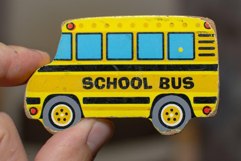 Feche acima de uma parte amarela do enigma do ônibus escolar do brinquedo gasto com uma mão adulta Conceptual imagens de stock
