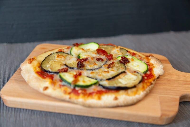 Feche acima de uma pizza com abobrinha, beringela e os tomates secos com mozzarella do gratin imagens de stock royalty free