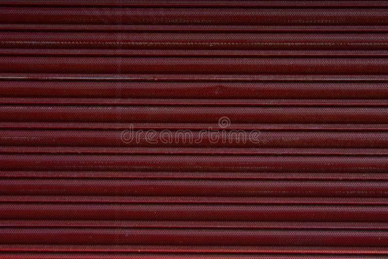 Feche acima de uma porta do obturador do rolo, fundo vermelho plástico da textura fotografia de stock royalty free