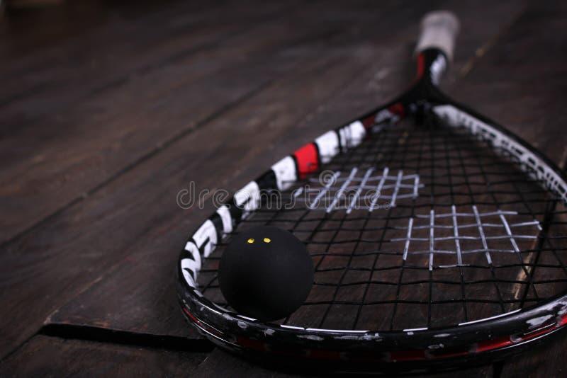 Feche acima de uma raquete e de uma bola de polpa no fundo de madeira fotografia de stock