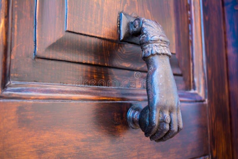 Feche acima de uma válvula de bronze com a forma de uma mão em uma madeira fotografia de stock
