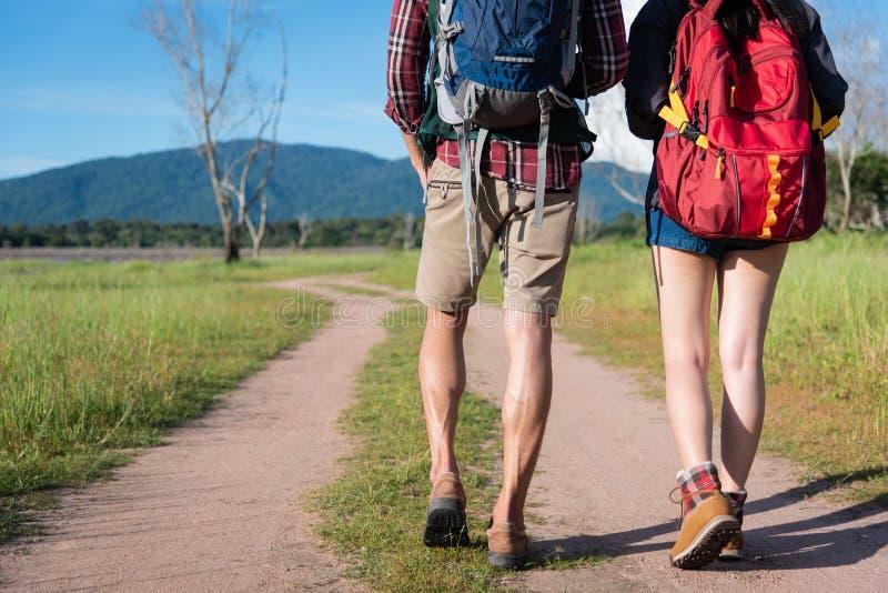 Feche acima de uns mais baixos pés de dois viajantes que andam ao longo do trajeto no na fotos de stock royalty free