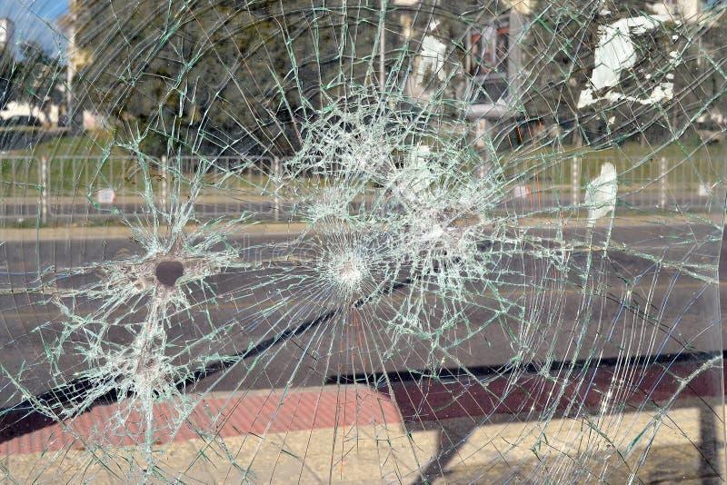 Feche acima de vidro de segurança quebrado com muitas quebras em uma parada do ônibus em uma rua da cidade imagem de stock