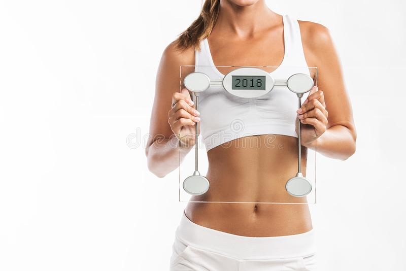 Feche acima do abdômen dos woman's, guardando uma escala do peso com um ano 2018 escrito nela imagem de stock