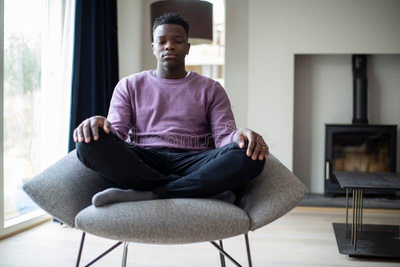 Feche acima do adolescente calmo que medita o assento na cadeira em casa imagens de stock royalty free