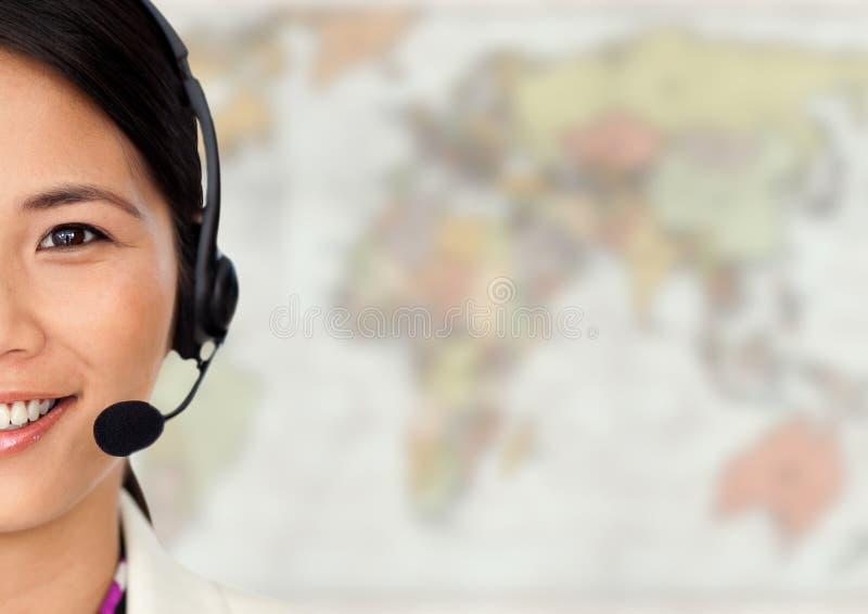 Feche acima do agente de viagens com os auriculares contra o mapa obscuro foto de stock