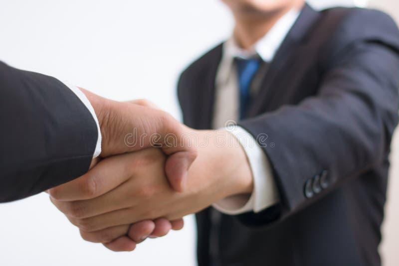 Feche acima do aperto de mão do homem de negócios do acionista com vendedor do sócio Homem de negócios que agita as mãos usando-s foto de stock