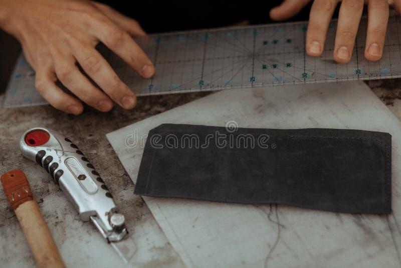 Feche acima do artesão de couro que trabalha com couro natural Mestre feito a mão no trabalho na oficina local Conceito feito a m fotos de stock royalty free