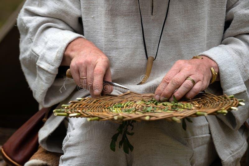 Feche acima do artesão que veste a roupa rural que faz a cesta de vime dos galhos Técnica de tecelagem feito a mão tradicional na foto de stock royalty free