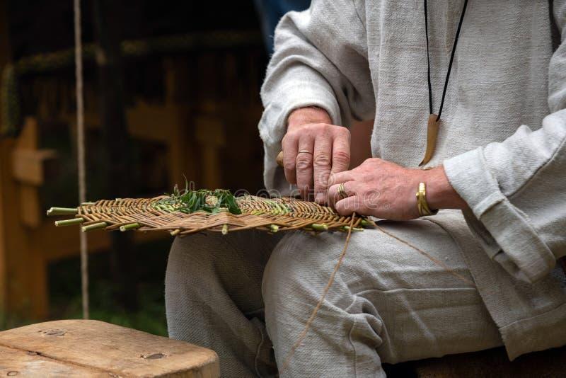 Feche acima do artesão que veste a roupa rural que faz a cesta de vime dos galhos Técnica de tecelagem feito a mão tradicional na imagem de stock