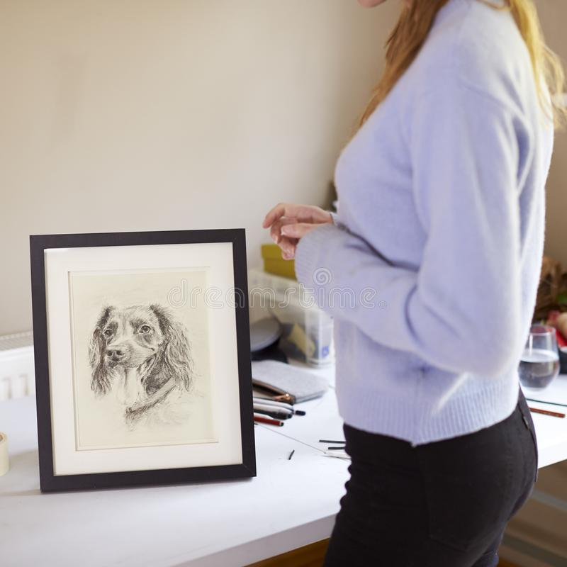Feche acima do artista adolescente fêmea Framing Charcoal Drawing do cão no estúdio imagens de stock royalty free