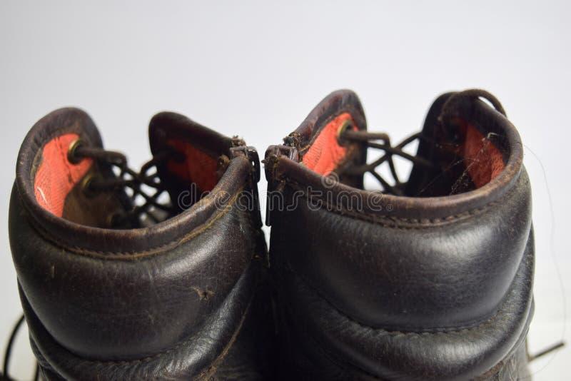 Feche acima do as botas velhas marrons isoladas no fundo branco fotos de stock royalty free