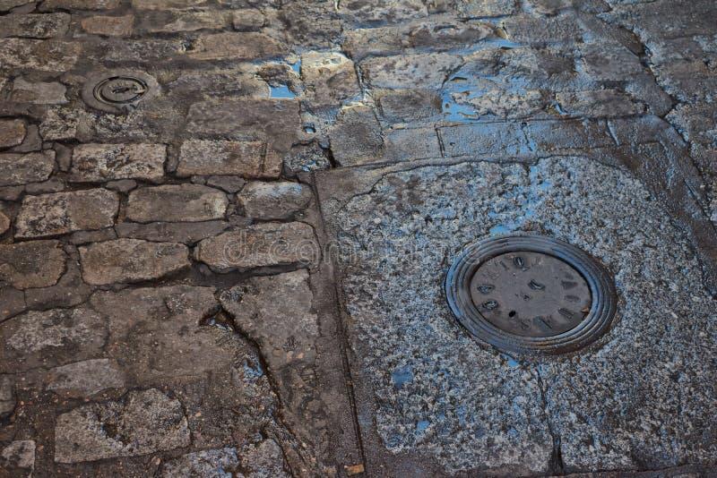 Feche acima do assoalho de pedra velho molhado com poças e tampas da fonte de água imagens de stock