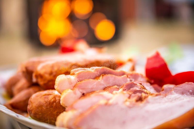 Feche acima do bacon, das salsichas e da paprika crus na bandeja colorida, preparada para o assado Com a grade de incandescência  imagem de stock
