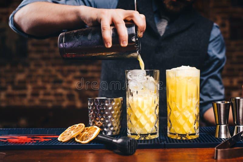 Feche acima do barman de trabalho Cocktail de derramamento do citrino sobre o gelo, detalhes alaranjados do cocktail fotografia de stock royalty free