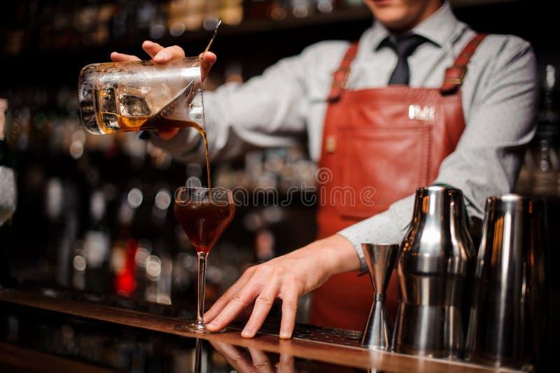 Feche acima do barman que derrama o cocktail vermelho brilhante do álcool no vidro extravagante imagens de stock
