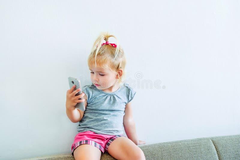 Feche acima do bebê pequeno bonito que guarda e que joga com a pedra de afiar do smartp que senta-se no sofá no fundo branco da p fotos de stock