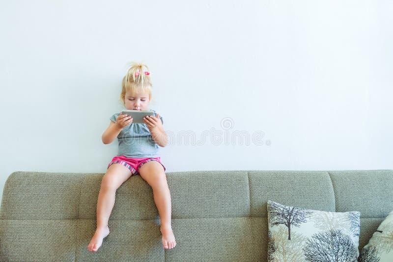 Feche acima do bebê pequeno bonito que guarda e que joga com a pedra de afiar do smartp que senta-se no sofá no fundo branco da p fotografia de stock