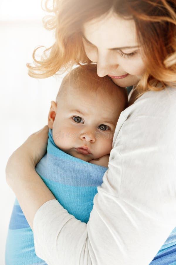 Feche acima do bebê pequeno doce que olha a câmera com seus olhos cinzentos grandes A mamã aconchega-se sua criança com ternura e fotos de stock