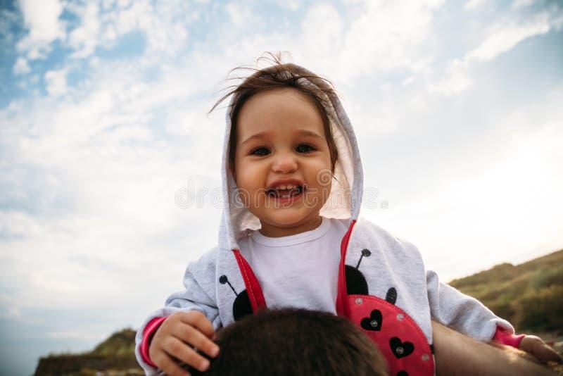 Feche acima do bebê pequeno feliz na capa que senta-se nos ombros do pai no fundo do céu imagem de stock royalty free