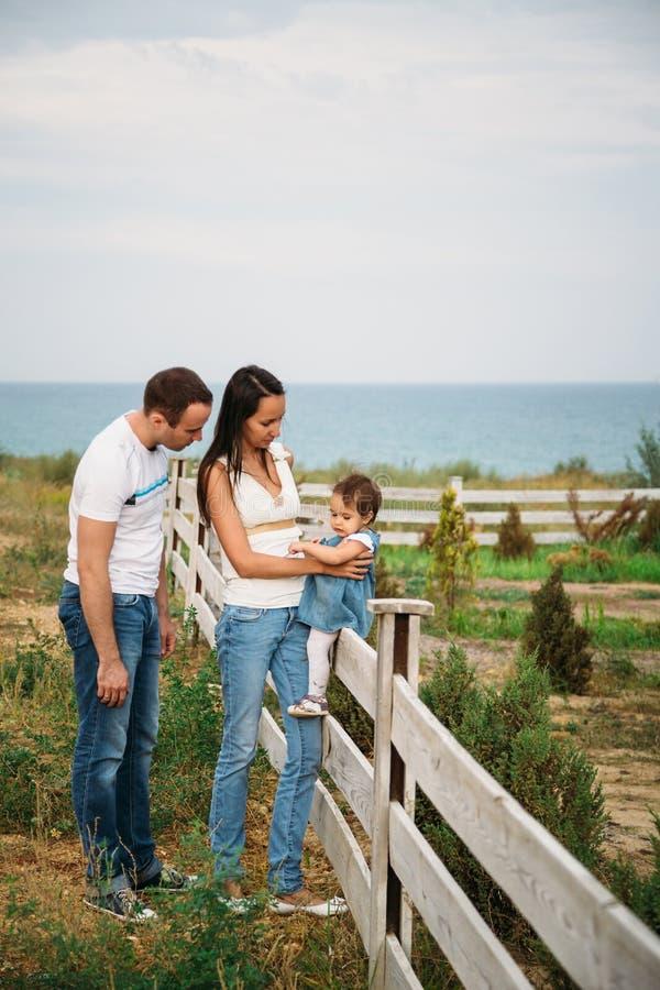 Feche acima do bebê pequeno na calças de ganga vestem o assento em uma cerca com mãe e pai próximo foto de stock