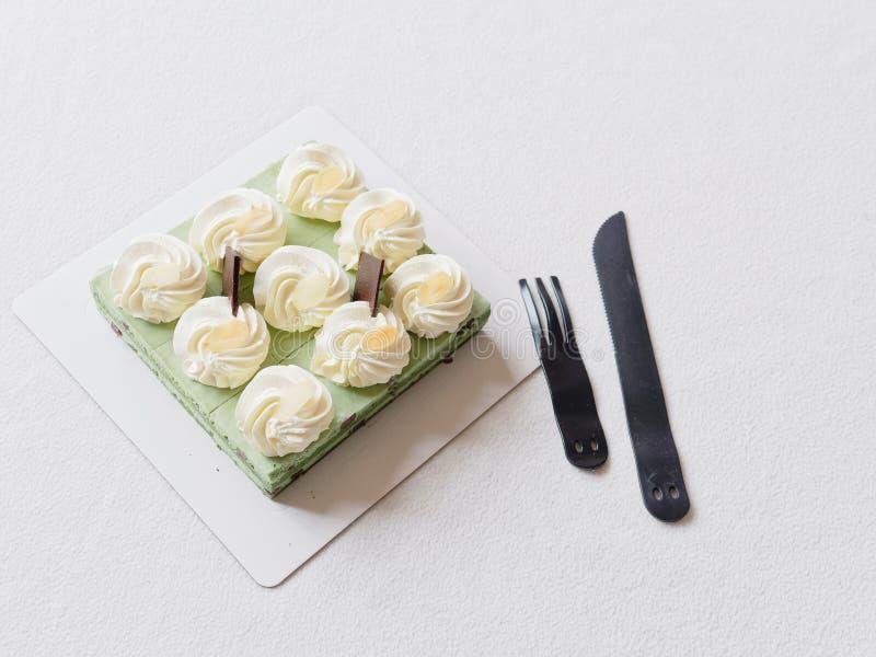 Feche acima do bolo de aniversário, faca e povos plásticos na toalha de mesa branca, alimento doce delicioso e conceito do feliz  fotografia de stock royalty free