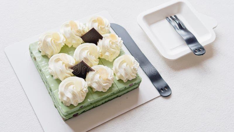 Feche acima do bolo de aniversário, faca e povos plásticos na toalha de mesa branca, alimento doce delicioso e conceito do feliz  imagem de stock