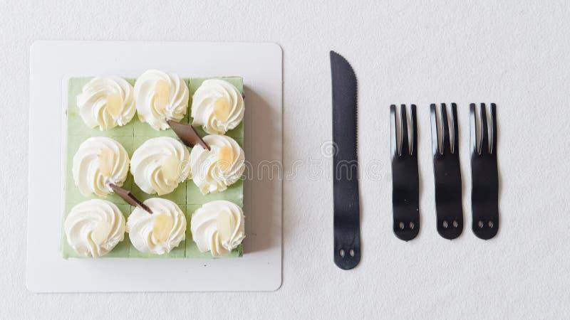 Feche acima do bolo de aniversário, faca e povos plásticos na toalha de mesa branca, alimento doce delicioso e conceito do feliz  imagem de stock royalty free