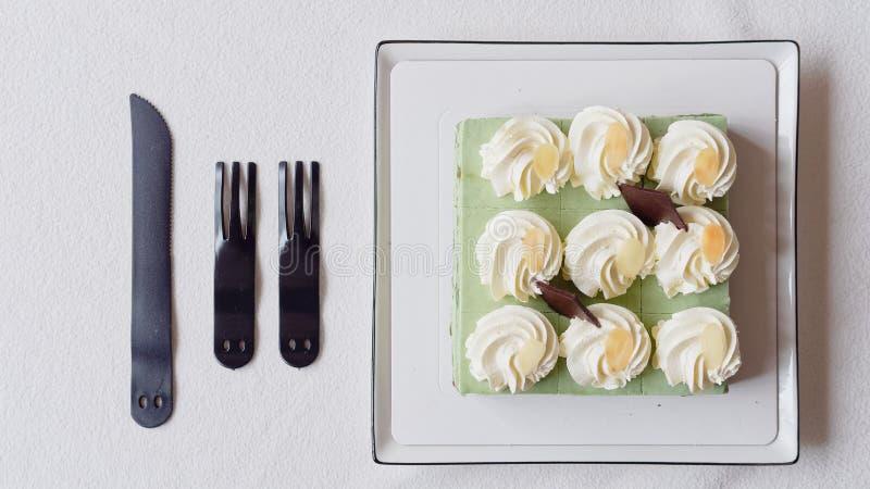 Feche acima do bolo de aniversário, faca e povos plásticos na toalha de mesa branca, alimento doce delicioso e conceito do feliz  fotos de stock