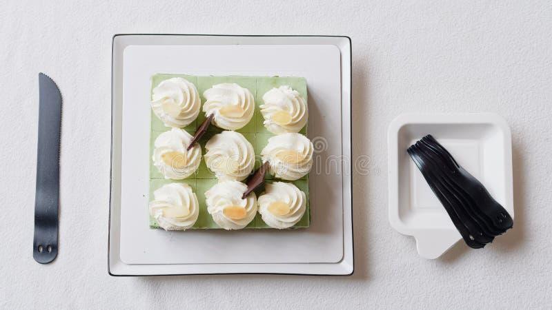 Feche acima do bolo de aniversário, faca e povos plásticos na toalha de mesa branca, alimento doce delicioso e conceito do feliz  fotos de stock royalty free