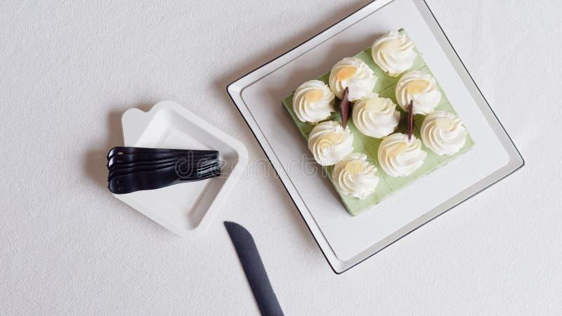 Feche acima do bolo de aniversário, faca e povos plásticos na toalha de mesa branca, alimento doce delicioso e conceito do feliz  foto de stock
