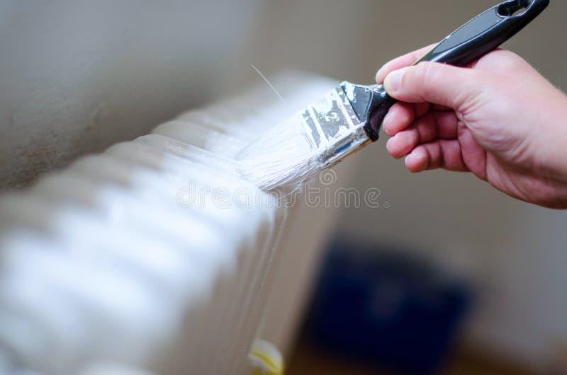 Feche acima do braço do pintor que pinta um radiador do aquecimento com rolo de pintura Mão profissional do trabalhador que guard imagem de stock