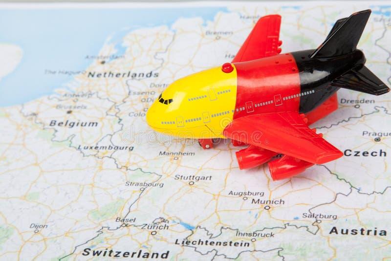 Feche acima do brinquedo do avião com bandeira alemão, aterrado no mapa de Europa conceito do curso fotografia de stock